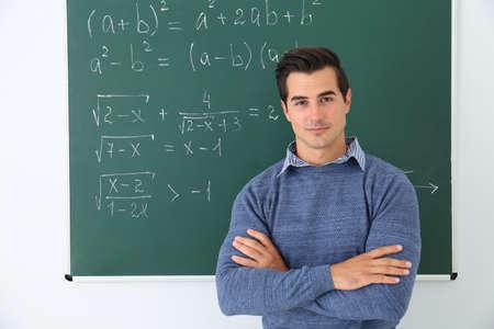 Young teacher near chalkboard with math formulas in classroom