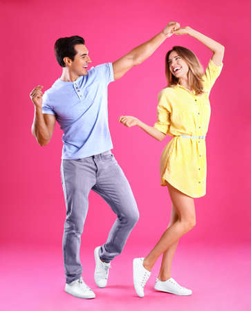 Beautiful young couple dancing on pink background