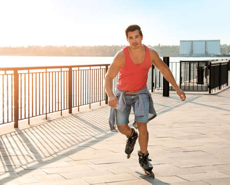 Handsome young man roller skating on pier near river, space for text Stock Photo