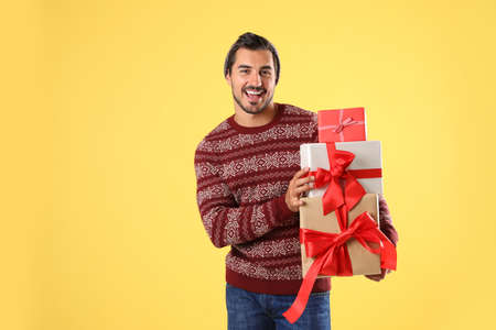 Happy man in Christmas sweater and hat holding gift boxes on yellow background Stock Photo