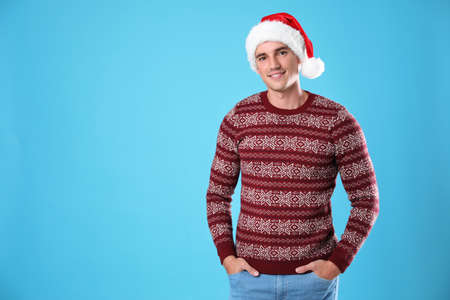 Portrait of young man in Christmas sweater and Santa hat on light blue background. Space for text