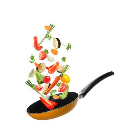 Muchas verduras diferentes cayendo en una sartén sobre fondo blanco.