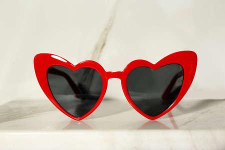 Heart shaped stylish sunglasses on light background Stok Fotoğraf