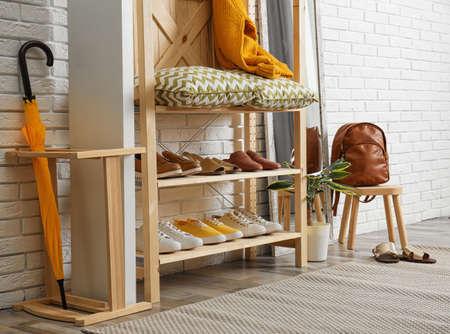 Stylish hallway interior with shoe rack near brick wall