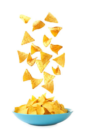 Delicious Mexican nachos chips falling into dish on white background Stock Photo