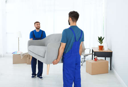 Young workers carrying sofa in room. Moving service Banque d'images