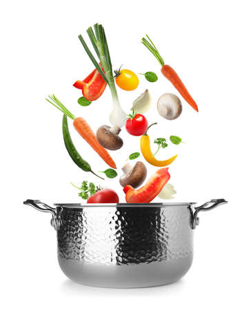 Many different vegetables falling into pot on white background