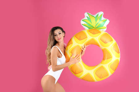 Pretty sexy woman in stylish bikini with inflatable ring on color background