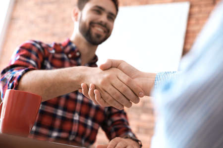 Business partners shaking hands after meeting, closeup