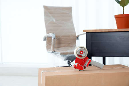 Box with adhesive tape dispenser and furniture in room. Moving service Banque d'images