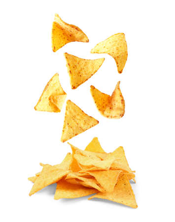 Delicious Mexican nachos chips falling into pile on white background