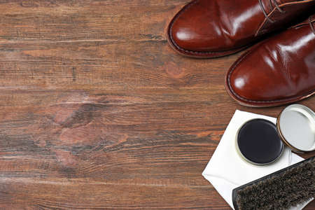 Flat lay composition with footwear and shoe shine kit on wooden background, space for text