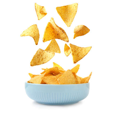 Delicious Mexican nachos chips falling into bowl on white background