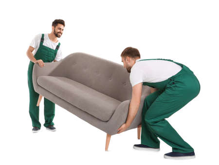 Young workers lifting sofa isolated on white. Moving service Stock Photo