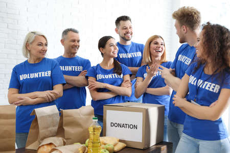 Team of volunteers near table with food donations indoors Banco de Imagens