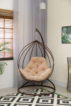 Comfortable swing chair with pillow in room interior