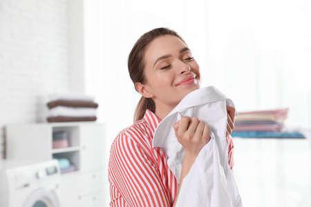Glückliche junge Frau mit sauberem Hemd zuhause. Waschtag