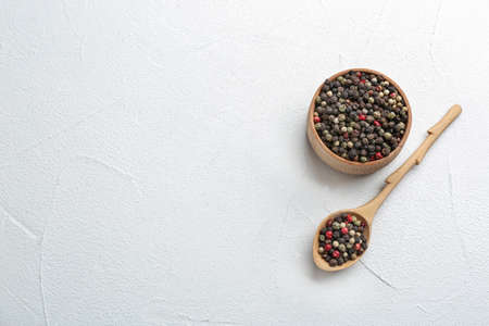 Bowl and spoon with different peppercorns on light table, top view. Space for text Фото со стока