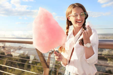 Young woman with cotton candy outdoors on sunny day Imagens - 128525091