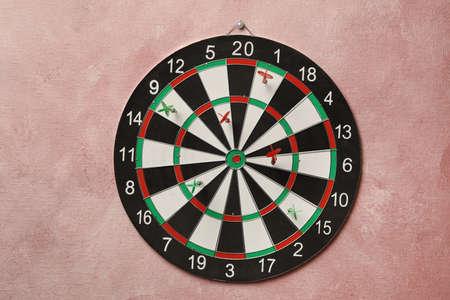 Arrows hitting dart board on pink wall 写真素材