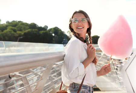 Young woman with cotton candy outdoors on sunny day. Space for text Imagens - 128525096
