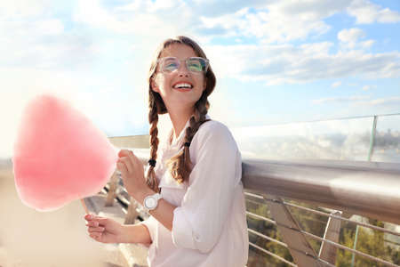 Young woman with cotton candy outdoors on sunny day. Space for text Imagens - 128525103