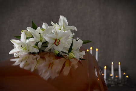 Wooden casket with white lilies in funeral home, closeup 스톡 콘텐츠