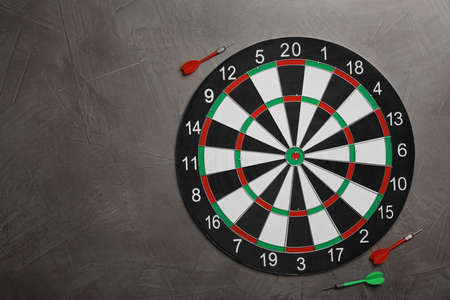 Dart board with color arrows on grey stone background, top view. Space for text Stock Photo