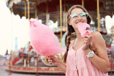 Young woman with cotton candy in amusement park