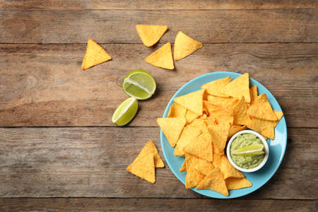 Plate with delicious mexican nachos chips, guacamole sauce and lime on wooden table, flat lay. Space for text Stock Photo