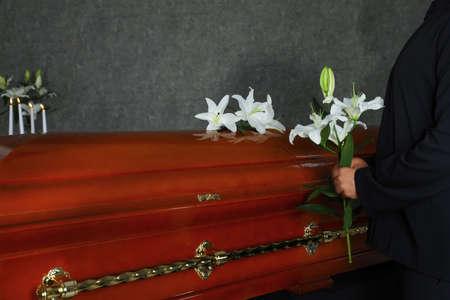 Junger Mann in der Nähe von Sarg mit weißen Lilien im Bestattungsinstitut Standard-Bild