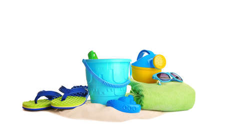 Set of plastic beach toys, accessories and pile of sand on white background