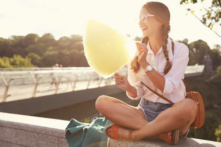 Young woman with cotton candy outdoors on sunny day. Space for text Imagens - 128525107