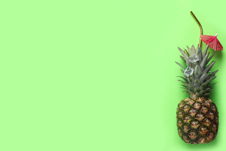 Creative composition with pineapple, ice, straw and cocktail umbrella on green background. Space for text Stock Photo