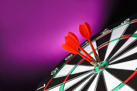 Red arrows hitting target on dart board against purple background. Space for text