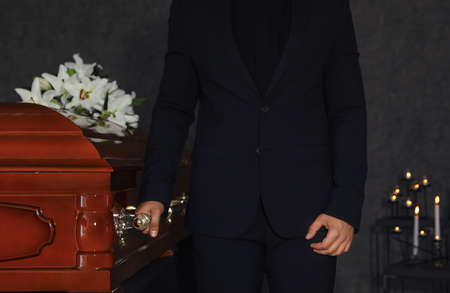 Młody człowiek niosący drewnianą trumnę w domu pogrzebowym, zbliżenie Zdjęcie Seryjne
