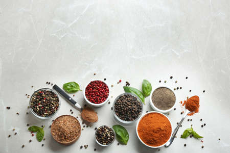 Flat lay composition with ground pepper and corns on marble table. Space for text