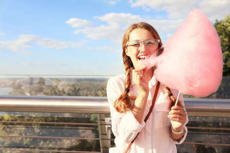 Young woman with cotton candy outdoors on sunny day. Space for text Imagens - 128525112