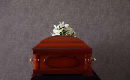 Wooden funeral casket with white lilies at grey wall Stock Photo