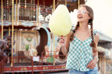 Young woman with cotton candy in amusement park. Space for text Stock Photo