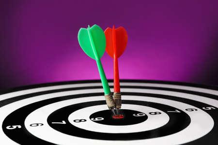 Arrows hitting target on dart board against purple background