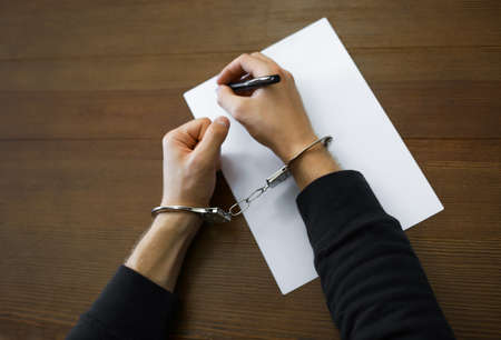 Criminal in handcuffs writing confession at desk, top view Imagens