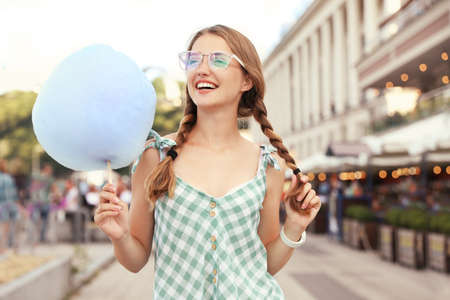 Young woman with cotton candy on city street
