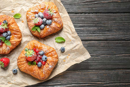 Fresh delicious puff pastry with sweet berries on dark wooden background, top view. Space for text