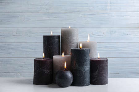 Set of burning candles on table against light wooden background