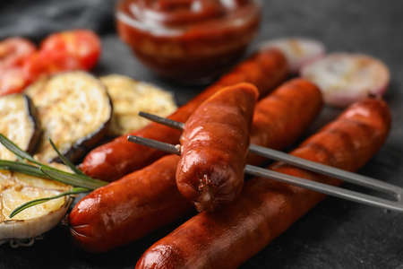 Delicious grilled sausages and vegetables on black table, closeup. Barbecue food