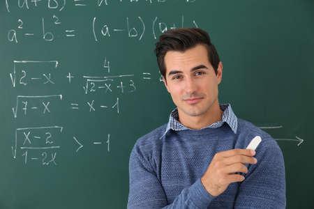 Young teacher near chalkboard with math formulas