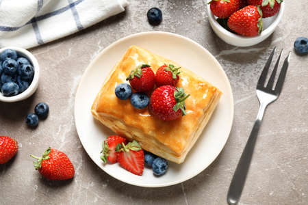 Fresh delicious puff pastry with sweet berries on grey marble table, flat lay