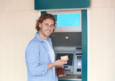 Young man with credit card near cash machine outdoors