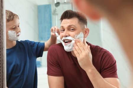 Son applying shaving foam on dad's face at mirror in bathroom